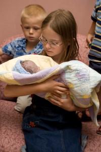 Rachel holding Dekar with Mel looking on.
